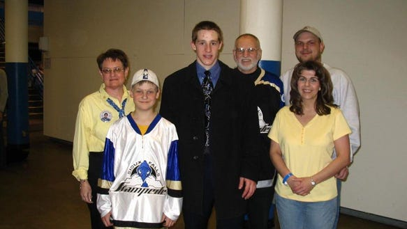 Carroll poses with Jerry and Ruth Menken and their extended family at the Sioux Falls Arena during his playing days with the Stampede.