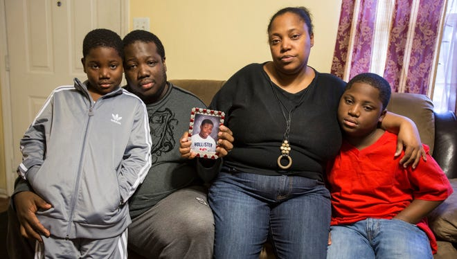 Brother Jayden Green, 8, father Wayne, mother Kendelynn and brother D'Ante, 11, gather around a photo of D'Andre Green, 16, who was shot and killed outside a community center in Ogletown, Del., on Saturday, Dec. 28, 2013.