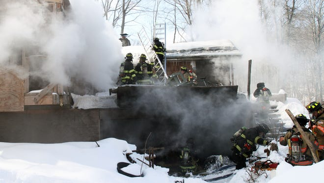 Goldens Bridge firefighters with mutual aid from many northern Westchester and Putnam departments battle a fire in a home on Lake Street in Goldens Bridge Feb. 25, 2015.