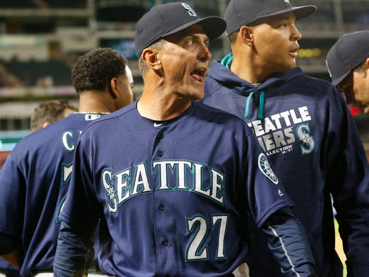 Seattle Mariners bench coach Tim Bogar (27) yells as he heads back to the dugout after Texas Rangers relief pitcher Tom Wilhelmsen hit Chris Iannetta with a pitch during the eighth inning of a baseball game, Tuesday, April 5, 2016, in Arlington, Texas. The Mariners won 10-2. (AP Photo/Jim Cowsert)