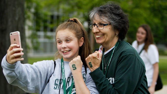 """Madison Speer, 12, of Brighton takes a selfie with grandma Joyce Flotkoetter of Pinckney June 28, 2017, to send to her dad during the Grandparents University event at Michigan State University.  """"I never got to experience college, so this is a fun and brand new experience for both of us,"""" Joyce said. Her son is an MSU grad. The event is a three-day program for alumni and grandchildren ages 8-12 to experience MSU where they attend classes, dine in cafeterias, and stay in dorms."""