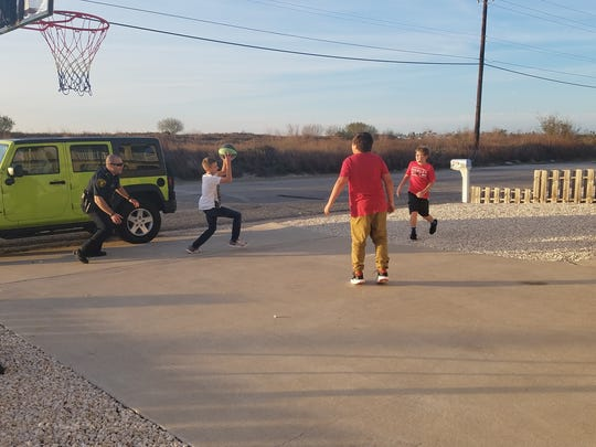 Corpus Christi Police Officer Salazar, Landon Swander, 11, and two of Landon's friends from the neighborhood play basketball  on Tuesday, Jan. 30, 2018.
