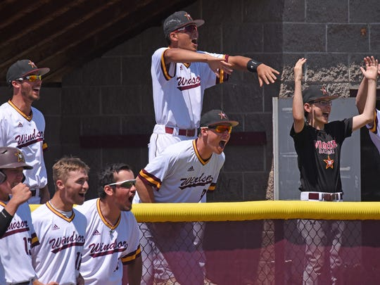 Players from the dugout erupt with joy as the Windsor
