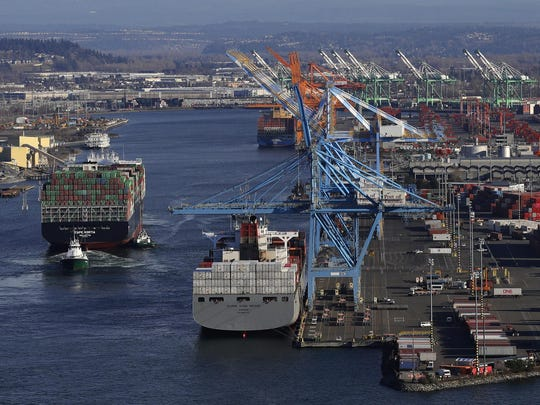 In this Tuesday, March 5, 2019, file photo the Cape Kortia container ship, left, heads into the Port of Tacoma in Commencement Bay in Tacoma, Wash.