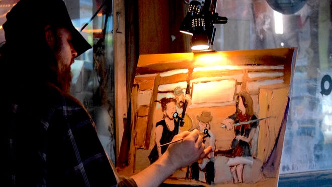 Artist Robby Amonett paints Cary Hudson and the Piney Woods Players while they perform recently at The Shed in Ocean Springs. Amonett will be one of the featured artists at Spring Art Walk on Saturday.