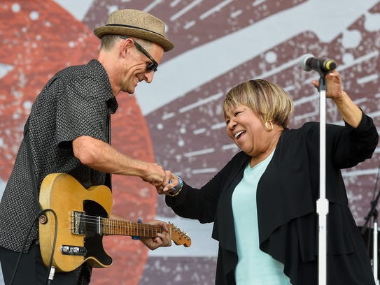 Mavis Staples bumps fists with guitar player Rick Holmstrom