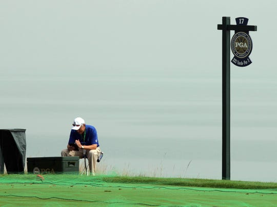 An official sits near the 17th hole tee at Whistling