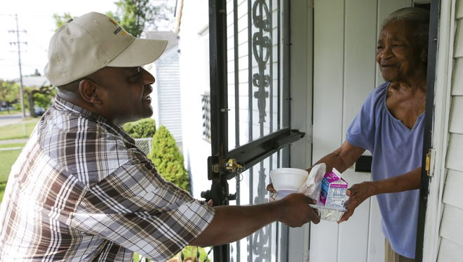 Meals on Wheels volunteer Fred Hodges delivers a meal  to Annie Lee Duncan last year.