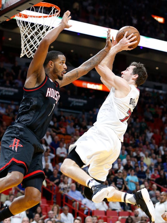 Miami Heat guard Goran Dragic, right, goes up for a shot against Houston Rockets forward Trevor Ariza during the second half of an NBA basketball game, Tuesday, Jan. 17, 2017, in Miami. Dragic had 21 points and eight assists as the Heat defeated the Rockets 109-103. (AP Photo/Wilfredo Lee)