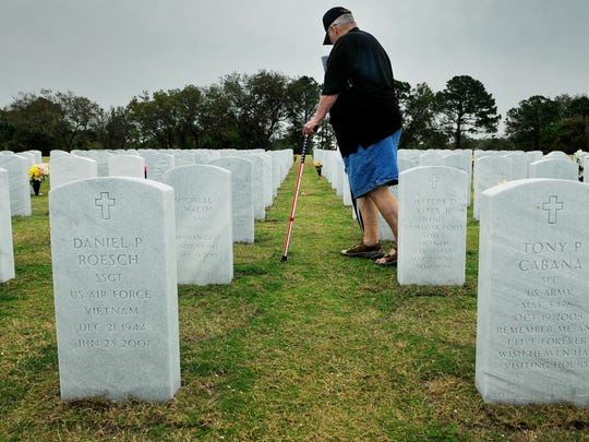 Tom Shoemaker of Titusville, who served in the Army and Air Force from 1955-80, pays his respect to fallen troops after a 2016 Vietnam War 50th anniversary ceremony at Cape Canaveral National Cemetery in Scottsmoor