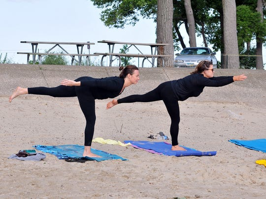 Students in Donna Lueke's meditative yoga class practice their balance during a session at East Harbor State Park beach on Tuesday morning.