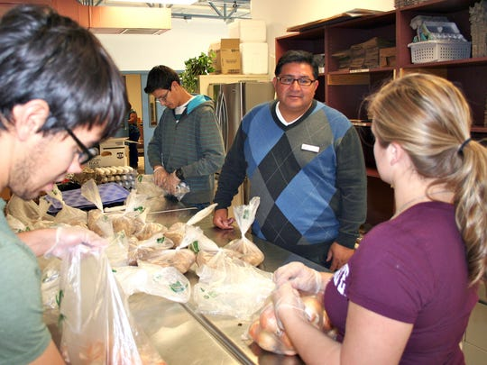 NMSU Housing and Residential Life volunteers David Schwartz, Matthew Salazar and Shannon Heinritz separate bulk potatoes, onions and eggs into family-size portions at Casa de Peregrinos, while Lorenzo Alba, executive director of the nonprofit food pantry, thanks them for their volunteer work.