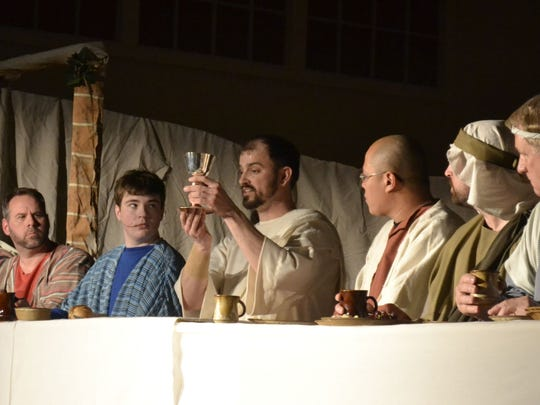 "Jesus of Nazareth, portrayed by Chris Rossmiller, center, holds up a cup of wine as an offering of his blood of the covenant to his disciples seated at the table during the annual reenactment of ""The Living Last Supper"" at Pilgrim Congregational Church in Ashwaubenon on Sunday night."