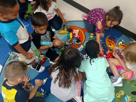 Pre-kindergarten students play with toys while in the