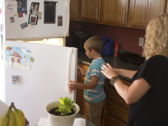 Connor Delaney looks to put away strawberries with his mother, Margaret, in the kitchen on June 24, 2016, in Phoenix. Connor has a rare genetic disease called phenylketonuria, or PKU. The metabolic disease prohibits him from having normal amounts of protein and forces him to stay on a strict diet for his entire life.
