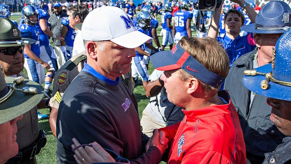 Memphis coach Justin Fuente speaks with coach Hugh Freeze after the Tigers defeated Ole Miss last season.
