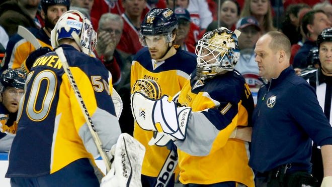 Buffalo Sabres goalie Nathan Lieuwen, left, comes into the game for injured goalie Jhonas Enroth during the second period against the Montreal Canadiens.