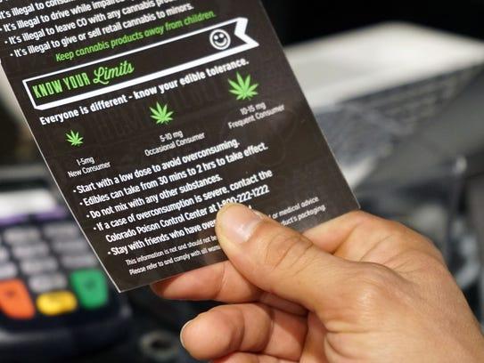 A customer at a Denver-area marijuana store holds a