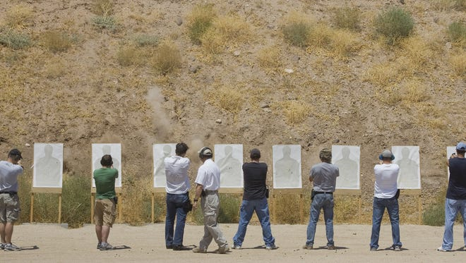 Students in a training session for a concealed weapon permit shoot paper targets as part of their successful completion of the course Sunday, July 18, 2010 at the Ben Avery Shooting Center in north Phoenix.