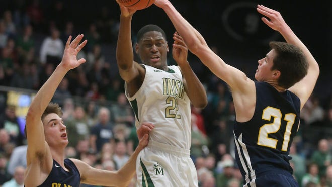 St. Vincent-St. Mary's Malaki Branham passes between North Olmsted's Gavin Dietrich, left, and Ryan Higginbotham during the fourth quarter in a Division I regional semifinal Wednesday at Rhodes Arena. The Irish won 47-37.