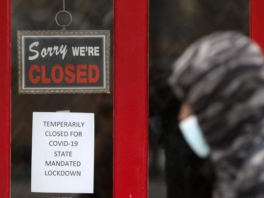 A pedestrian walks by The Framing Gallery, closed due to the COVID-19 pandemic, in Grosse Pointe, Mich., Thursday, May 7, 2020. Michigan Gov. Gretchen Whitmer said Thursday that auto and other manufacturing workers can return to the job next week, further easing her stay-at-home order while extending it through May 28 because of the coronavirus pandemic. (AP Photo/Paul Sancya)