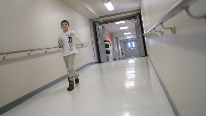 Nine-year-old Ryan Parker, a fourth-grader at Cedar Lane Elementary School, walks through the hall that connects modular classrooms to the main building.