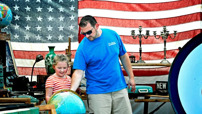 Greg Tisdale shows his daughter Graceland the world (actually a globe) at the Nashville Flea Market.
