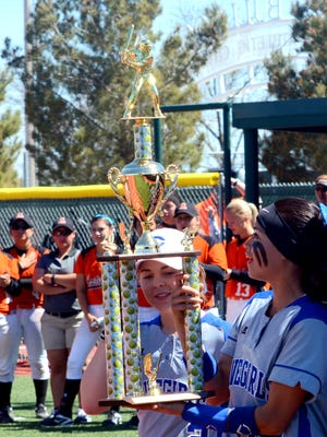 Carlsbad's Emilee Smedley (2) and Teddi Garcia (14) bring the consolation championship trophy back to the Cavegirls dugout after Saturday's win over Artesia.