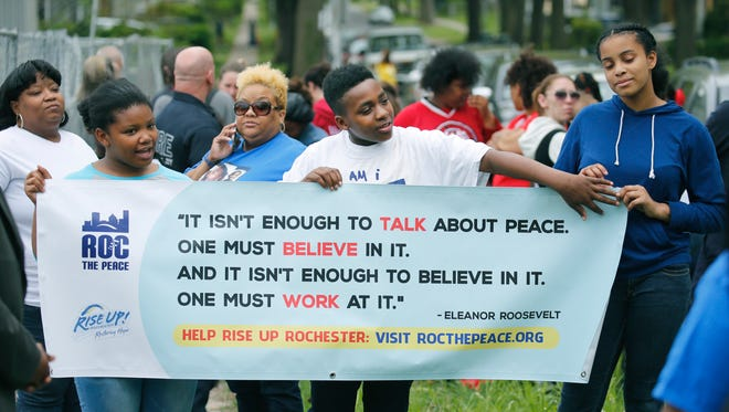 Jaiona Lester, 11, Jamier Ridgeway, 12, and Jahniya Williams, 12, hold a sign as participants gathered for a Stop the Violence Walk at the Boys and Girls Clubs of Rochester.