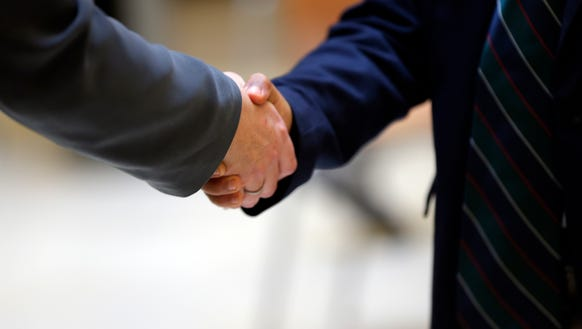 A student shakes hands with a judge.