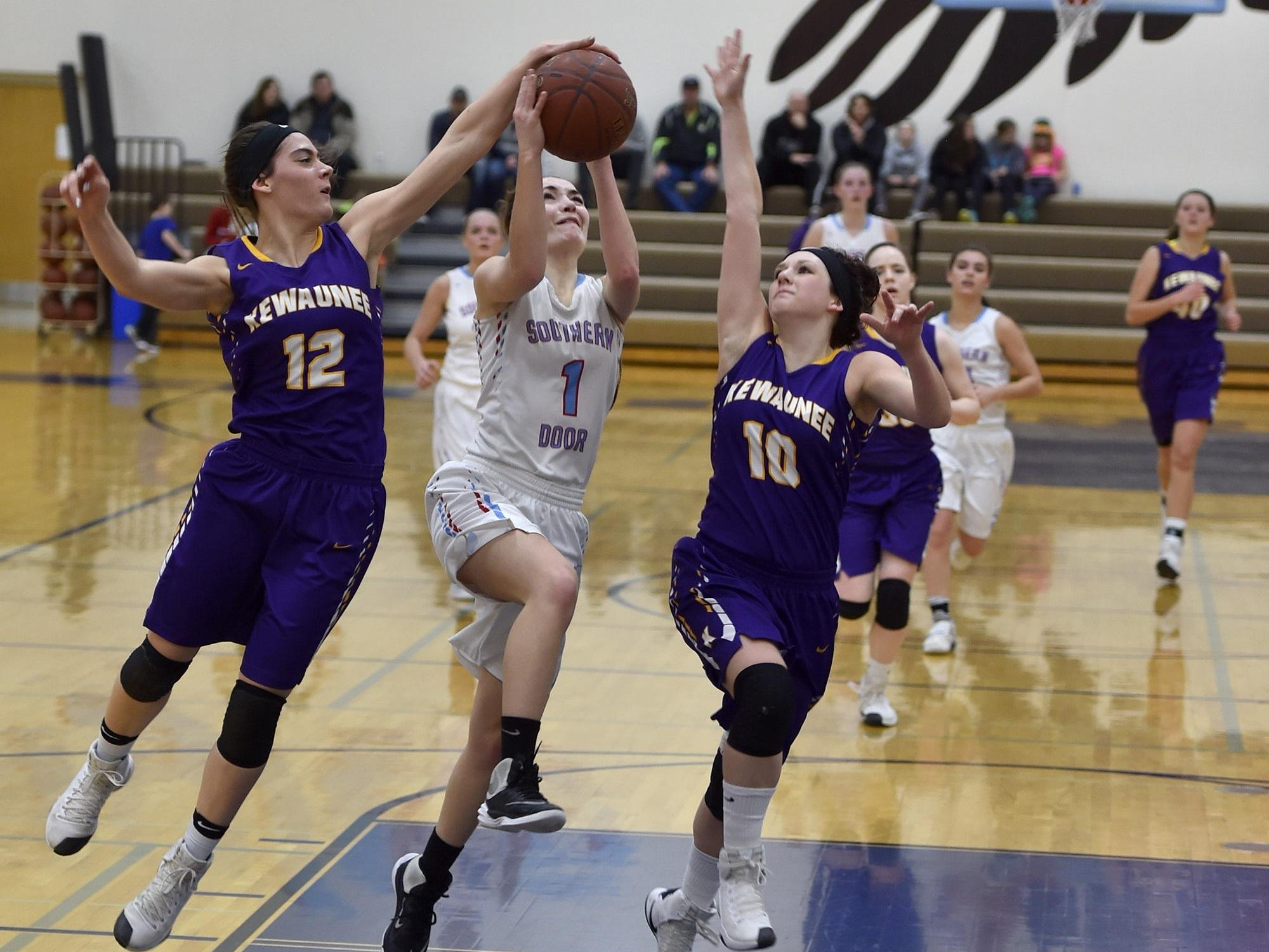 Southern Door's Katie Guilette drives the lane while being defended by Kewaunee's Brooke Geier, left, and McKenna Rentmeester on Friday during a Packerland Conference girls basketball game Friday.