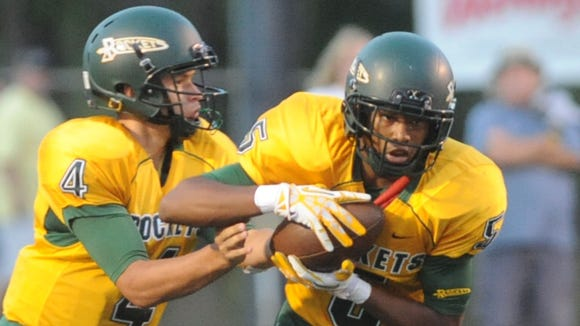 Rico Dowdle, right, takes a handoff from Levi Ledford during a 2013 game.