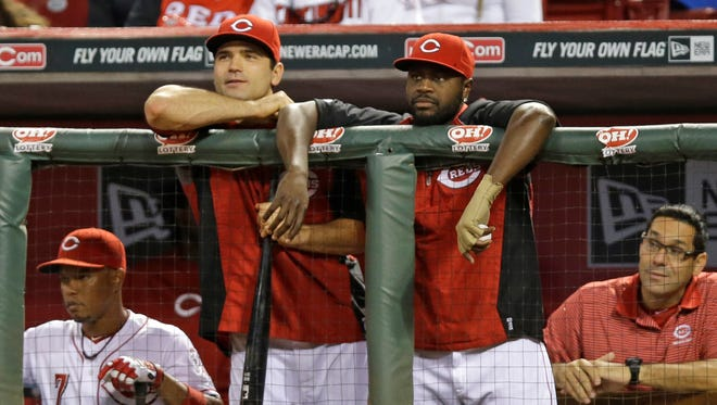 Cincinnati Reds' Joey Votto, center left, and Brandon Phillips, center right, watch from the dugout during a baseball game against the Arizona Diamondbacks, July 28, 2014, in Cincinnati.