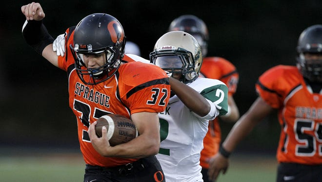 Sprague High School's Matt Kleinman is tackled by McKay's Demeris Bailey during the first quarter of their game on Friday, Sept. 12, 2014, in Salem, Ore.
