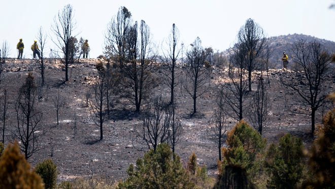 Firefighters inspect a burned over ridge from the Yarnell Hill Fire near Peeples Valley, Ariz., on Wednesday, July 3, 2013.