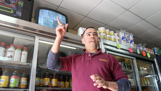 Domingo Moronta talks about the security cameras that he has installed in his deli in White Plains, N.Y., as a television monitor displays what the cameras see on Tuesday, Feb. 11, 2014. Moronta installed his four-camera digital video system four years ago. He said it will comply with the new law.