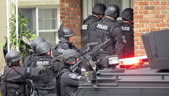 "Nassau County (N.Y.) police officers enter a home in Long Beach, N.Y., on Tuesday, April 22, 2014,  in search of an armed killer, based on a phone call that turned out to be a hoax. The practice of making such hoax calls, which bring out SWAT teams, has become known as ""swatting."""