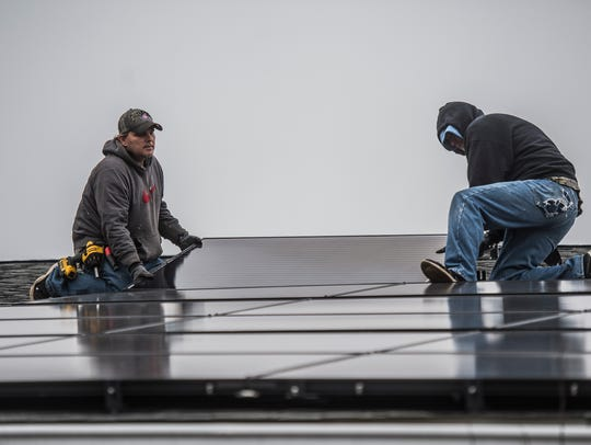 Crew members from Rectify Solar installs solar panels