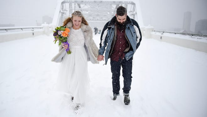 Jessica Reed and John Pyle depart after their wedding ceremony on the John Seigenthaler Pedestrian Bridge during a snow storm, Friday, Jan. 22, 2016, in Nashville, Tenn.