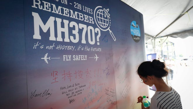 A girl writes a condolence message during the Day of Remembrance for MH370 event in Kuala Lumpur, Malaysia, on March 3, 2018.