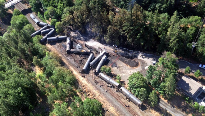 This aerial view provided by the Washington State Department of Ecology shows scattered and burned oil tank cars, Saturday, June 4, 2016, after the train derailed and burned near Mosier, Ore., Friday.