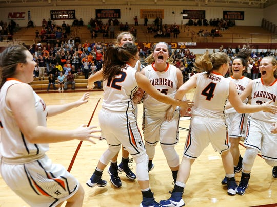Harrison players celebrate after defeating county rival McCutcheon 46-42 OT to win the 2016 Girls J&C Hoops Classic Saturday, November 19, 2016, at McCutcheon High School.