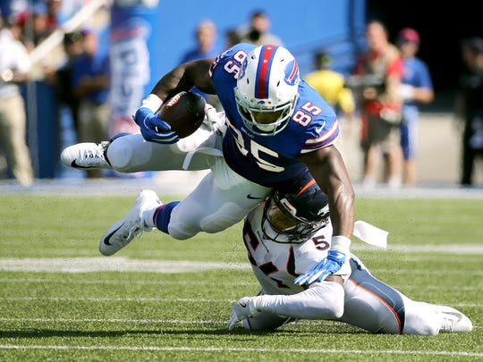 Bills tight end Charles Clay is tackled by Denver's Brandon Marshall after catching a pass over the middle.