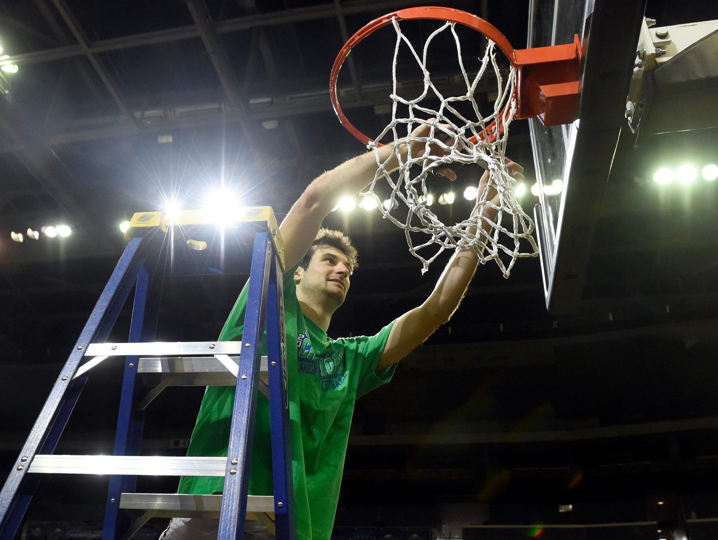 Adam Eberhard of Bellarmine cuts down a portion of the net after helping his team win the Great Lakes Valley Conference championship in Evansville in 2017.