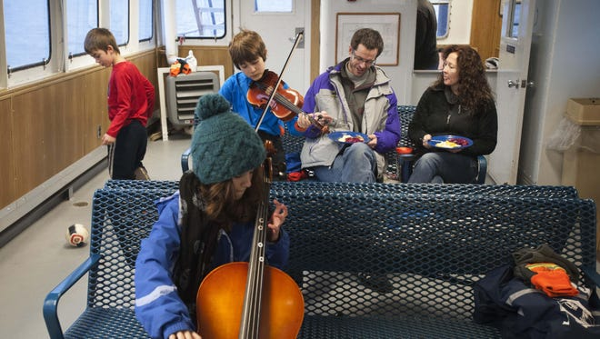 Ken Hughes and Susie Smith commute with their children Feb. 1, 2016, from Essex, N.Y., across Lake Champlain via ferry to Vermont. They finish breakfast in the passenger cabin while Oliver Hughes, 7, from left, plays with a ball, and Charlotte Hughes, 10, and Wyatt Trzaskos, 10, practice their music.