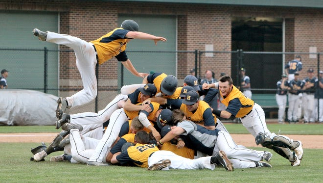 Hartland players pile up on Brett Oliver as they celebrate winning the  2015 state baseball championship.