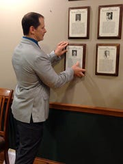 Dallastown High wrestling coach Dave Gable puts his York Area Sports Hall of Fame plaque on the wall at Insurance Services United.