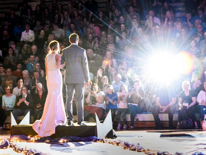 A couple pauses for photos during grand march Saturday,