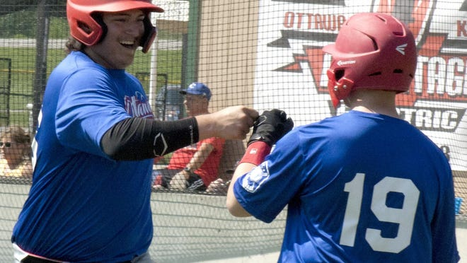 Ottawa Arrows catcher Antonio Espinosa fist bumps with Ryan Laurie after scoring a run against Topeka on Saturday at Harvey M. Drake field. Espinosa spearheaded the offense with a couple of hits in Ottawa's 11-3 victory.