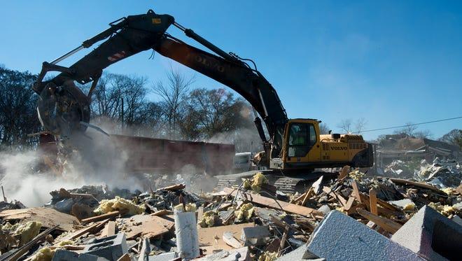 Mitchell Ford, Britt Demolition employee, uses an excavator to remove debris while helping demolish Head Elementary on Atlanta Highway in Montgomery, Ala., on Wednesday, Jan. 28, 2015.